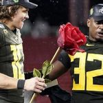 QB Justin Herbert holds a rose